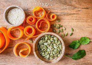 Pumpkin seeds and sesame seeds in bowls.